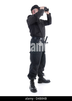 Security man wearing black uniform looking through binocular, shot on white - Stock Photo
