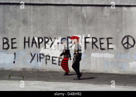 A couple of Punk Rockers walking passed CND graffiti. London England UK. Circa 1980's - Stock Photo