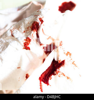 A white napkin has red dots from nose bleeding. - Stock Photo
