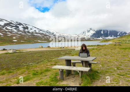 Young girl working on a laptop among mountains, Norway - Stock Photo