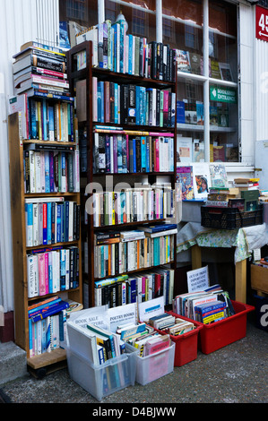 Books stacked on shelves and in boxes outside a secondhand bookshop. - Stock Photo