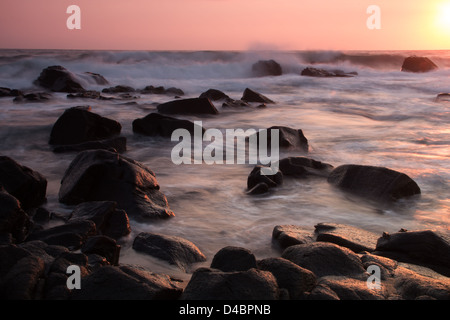 A slow exposure of waves crashing over rocks on a Ballito beach, Kwazulu Natal, warm colors from the sunrise in - Stock Photo