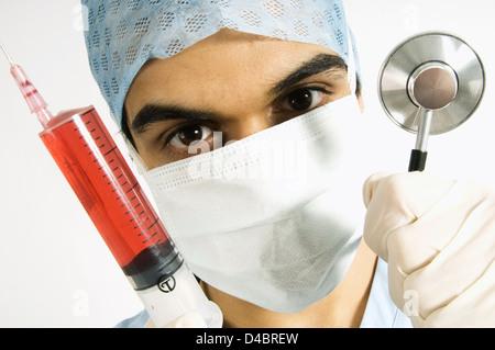 Portrait of surgeon holding up syringe and stethoscope to camera - Stock Photo