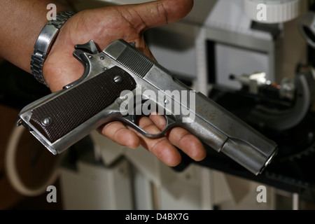 Man's hand holding revolver. Discarded gun found at a crime scene. - Stock Photo