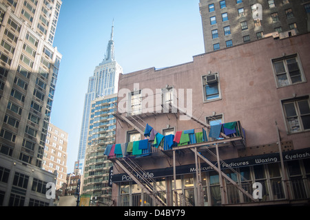 A yoga studio in Midtown Manhattan in New York airs out their yoga mats on a fire escape - Stock Photo