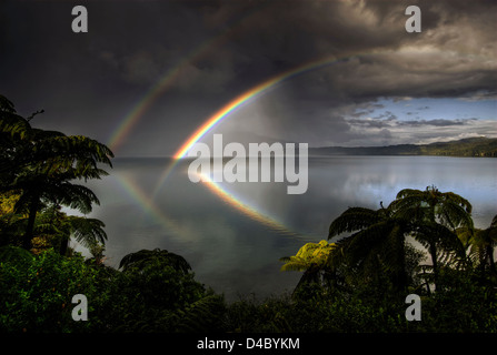 Double rainbow reflected in Lake Tarawera, Rotorua, New Zealand - Stock Photo