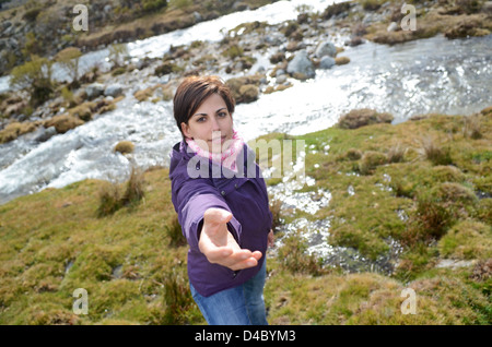 Young woman asking for help to climb in the mountain
