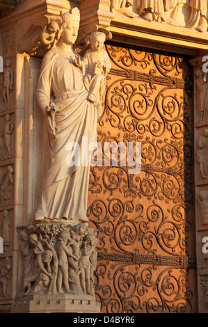 Our Lady of Paris. A statue of Mary and the infant Jesus on the trumeau of the Portal of the Virgin. The West Front - Stock Photo