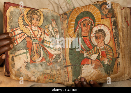 An Ethiopian Orthodox priest holds a book showing separate images of St George and the virgin Mary with the young - Stock Photo