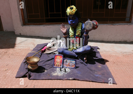 A young man dressed up as Shiva is begging for alms in Gangotri. - Stock Photo