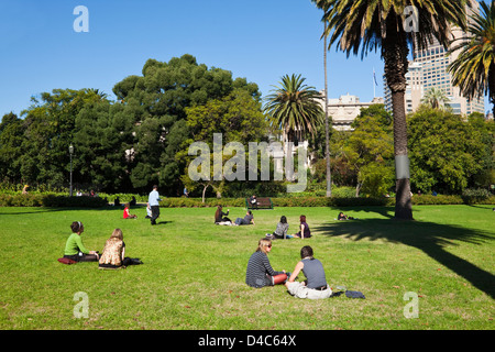 City workers relaxing on the lawn at Carlton Gardens. Fitzroy, Melbourne, Victoria, Australia - Stock Photo