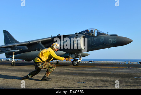 A US Navy Aviation Boatswain directs a AV-8B Harrier jet fighter aircraft to launch from the flight deck of the - Stock Photo