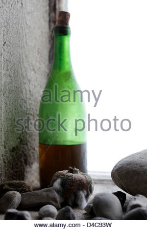 old wine bottle with molding passion fruit and stones near window - Stock Photo