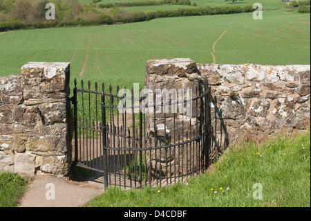 wrought iron kissing gate and kent ragstone wall leading out towards footpath across field of wheat crop countryside - Stock Photo