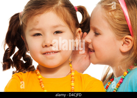 Closeup of two little 6-7 years old Asian and Caucasian girls gossip telling secrets mouse to ear, isolated on white - Stock Photo