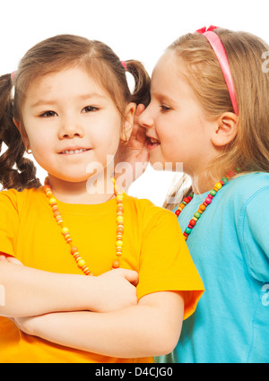Two little 6-7 years old Asian and Caucasian girls whisper telling secrets mouse to ear, isolated on white - Stock Photo