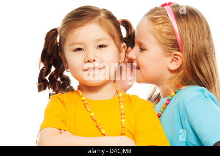 Close portrait of two little 6-7 years old Asian and Caucasian girls whisper telling secrets mouse to ear, isolated - Stock Photo