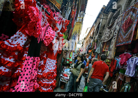 Tourists shop in a narrow alley full of stalls in the historic centre of Granada, Spain, 20 October 2007. Photo: - Stock Photo