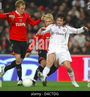 Munich's French defender Willy Sagnol (R), Hanover's Mike Hanke (C) and Jan Rosenthal (L) vie for the ball during - Stock Photo