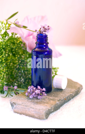 Blue glass bottle and lavender and orchid in a flower vase - Stock Photo