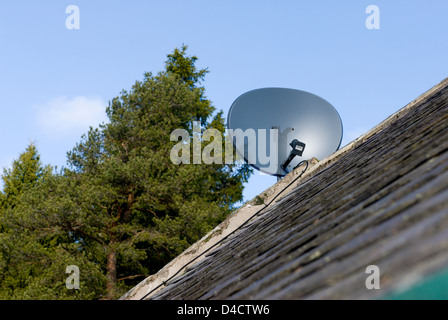 Satellite aerial dish on a remote house in rural Aberdeenshire - Stock Photo