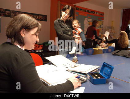 Voluntary worker Izmira Dervisoska (L) talks to young mother Jasmin Akcagear with her son Daniel in the multigenerational - Stock Photo