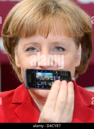 German Chancellor Angela Merkel poses with a SonyEricsson mobile phone at the IT trade fair CeBIT  in Hanover, Germany, - Stock Photo