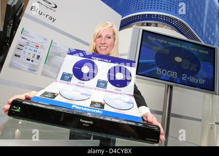 Model Julia presents a Panasonic DMP-BD 30 Blu-ray Disc player (bottom) and various rewritable Blu-ray discs at - Stock Photo