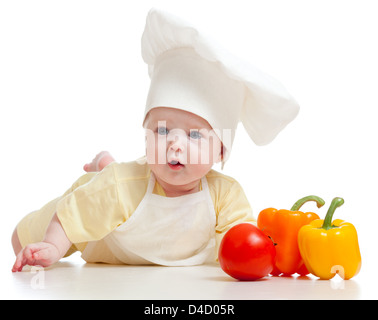 baby wearing a chef hat with healthy food vegetables, isolated on white - Stock Photo