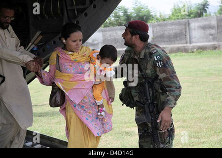 Members of the Pakistan Military Help Civilians Unload from a U.S. Army Helicopter - Stock Photo