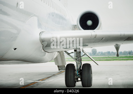 wing and engine of passenger airplane in airport - Stock Photo
