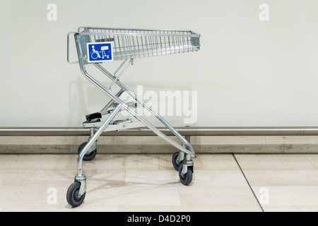 shopping trolley in supermarket with blue disabled sign - Stock Photo