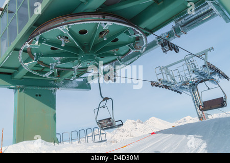 big chairlift wheel in italian ski area on snow covered alps - Stock Photo
