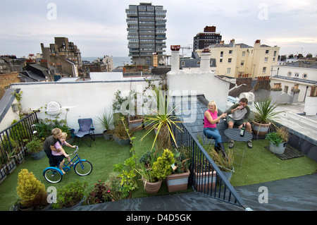 An urban family in the rooftop garden of their home in the city of Brighton and Hove with the sea in the distance. - Stock Photo