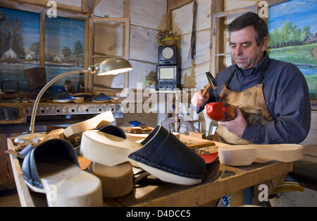 Clogs manufacturer Manfred Karolczak works a piece of lumber in his workshop in Burg, Germany, 14 April 2008. The - Stock Photo