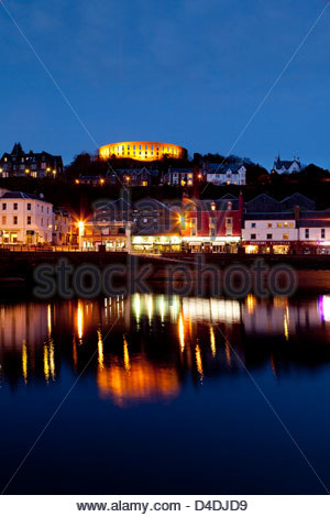 A view across the bay of Oban at dusk with McCaig's Tower prominent on the hill overlooking the town. Argyll, Scotland - Stock Photo