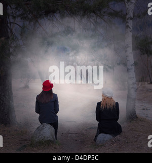 two girls sitting on stones in a forest - Stock Photo