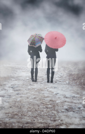 two girls with colourful umbrellas are walking in the mist - Stock Photo