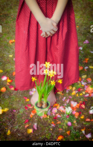 a girl is standing in front of daffodils - Stock Photo