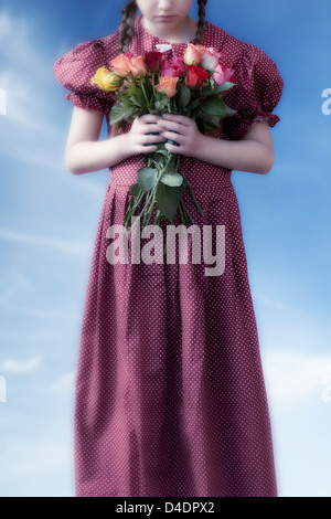 a girl in a red dress holding a bouquet of flowers - Stock Photo