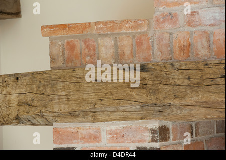 Close up of a beautiful old wooden beam being used as part of a fireplace in a newly converted barn in rural England. - Stock Photo