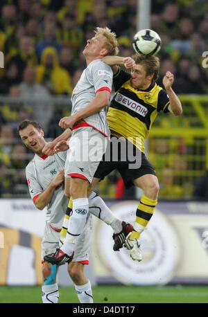 Dortmund's Jakub Blaszczykowski (R) vies for the ball with Hanover's Mike Hanke during the Bundesliga match Borussia - Stock Photo