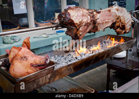 Hog roast on a barbecue spit, UK - Stock Photo