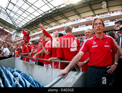 Cologne's head coach Christoph Daum (R) stays cool while team and fans celebrate winning the German Bundesliga 2nd - Stock Photo