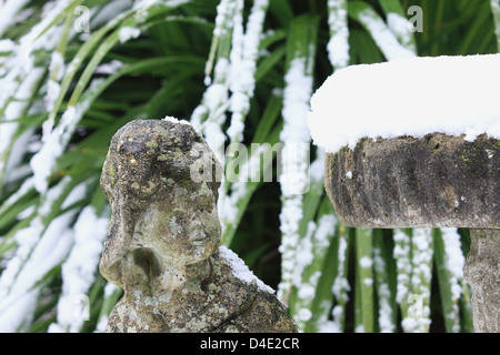 A garden statue apparently looking up at a mound of snow piled on top of a bird bath. Snow covered leaves in the - Stock Photo