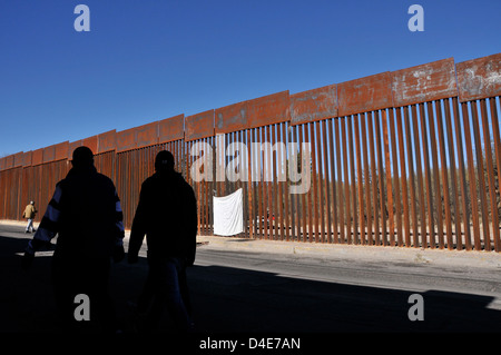 Men in Mexico, pass the border wall where a US Border Patrol agent in Nogales, Arizona, USA, shot a youth in Mexico. - Stock Photo