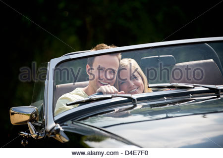 A young couple driving a black sports car - Stock Photo