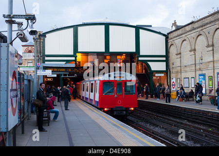 London District line tube underground train is leaving West Brompton station. People waiting on platform for another - Stock Photo
