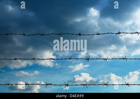 Barb wire fence and blue sky background - Stock Photo