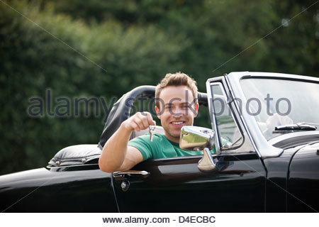 A young man sitting in a black sports car holding the keys - Stock Photo